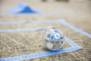 Sphero robot in a taped maze on carpet.