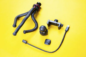 a tripod, ball-shaped camera, cord and phone holder on a yellow surface