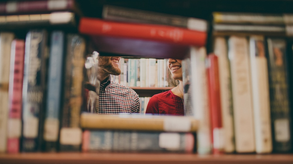 two people smiling, framed by books stacked on a shelf