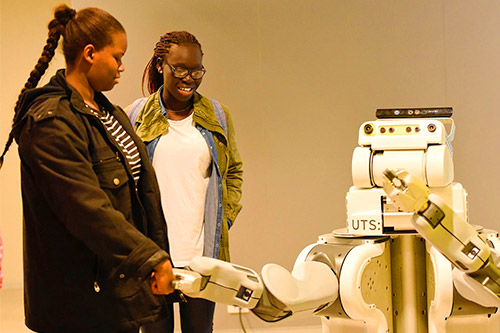 Two female students learn about social robotics
