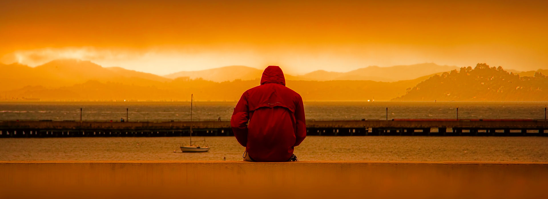 A person wearing a hoodie facing into a sunset.