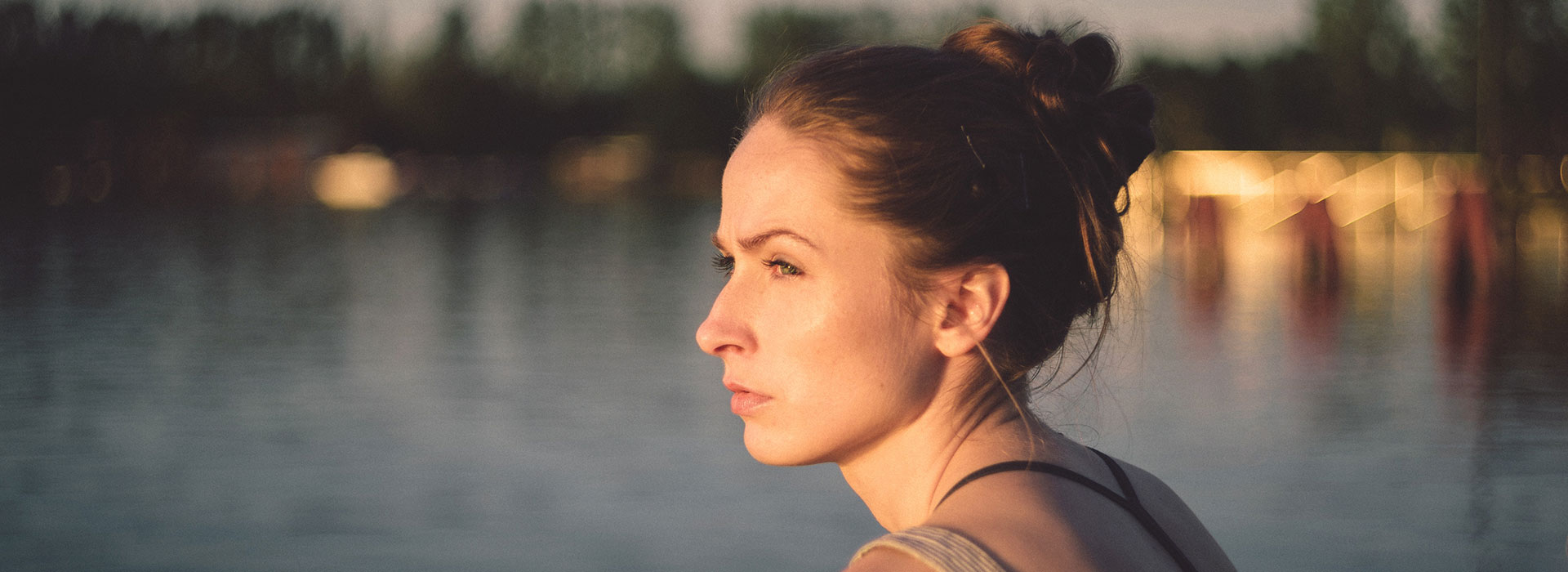 A side profile of a young woman looking pensively out towards the water.