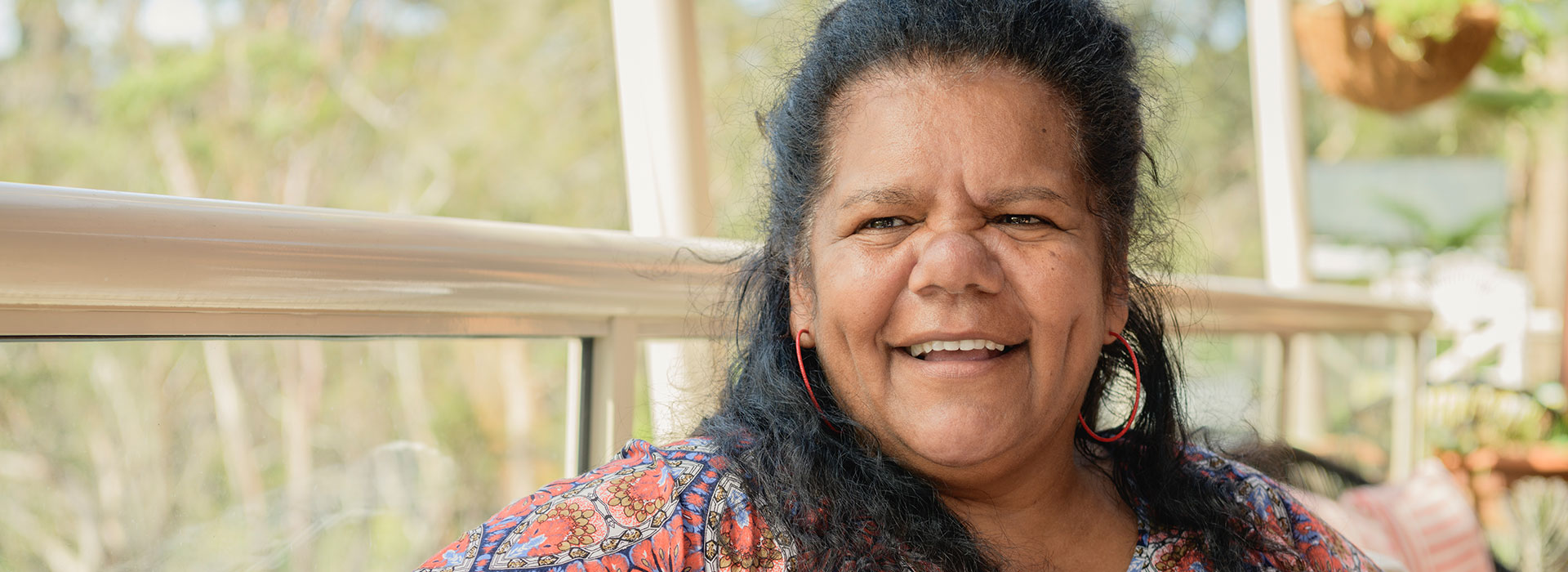 Indigenous Australian woman smiling off camera. Behind her is bush land.