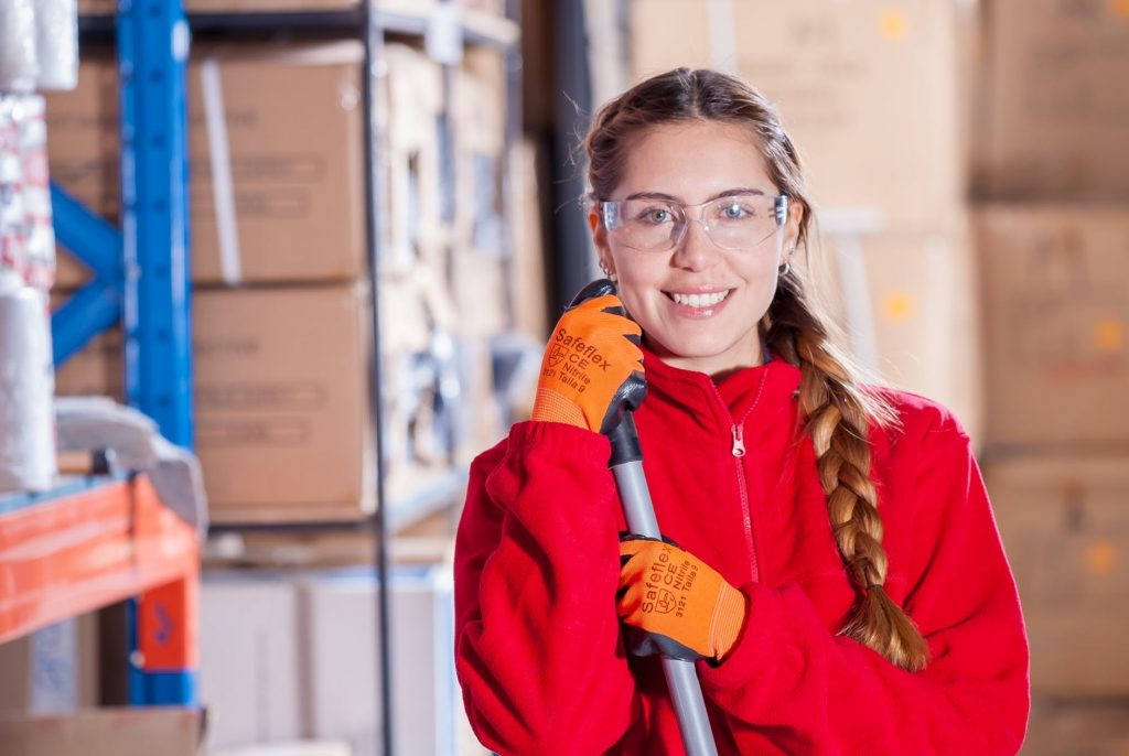 Young woman in red top holding broom in warehouse