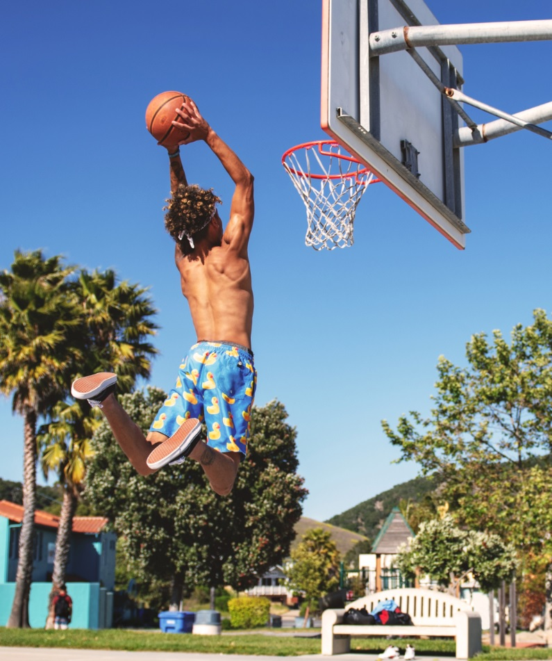 young man shooting basketball through hoop