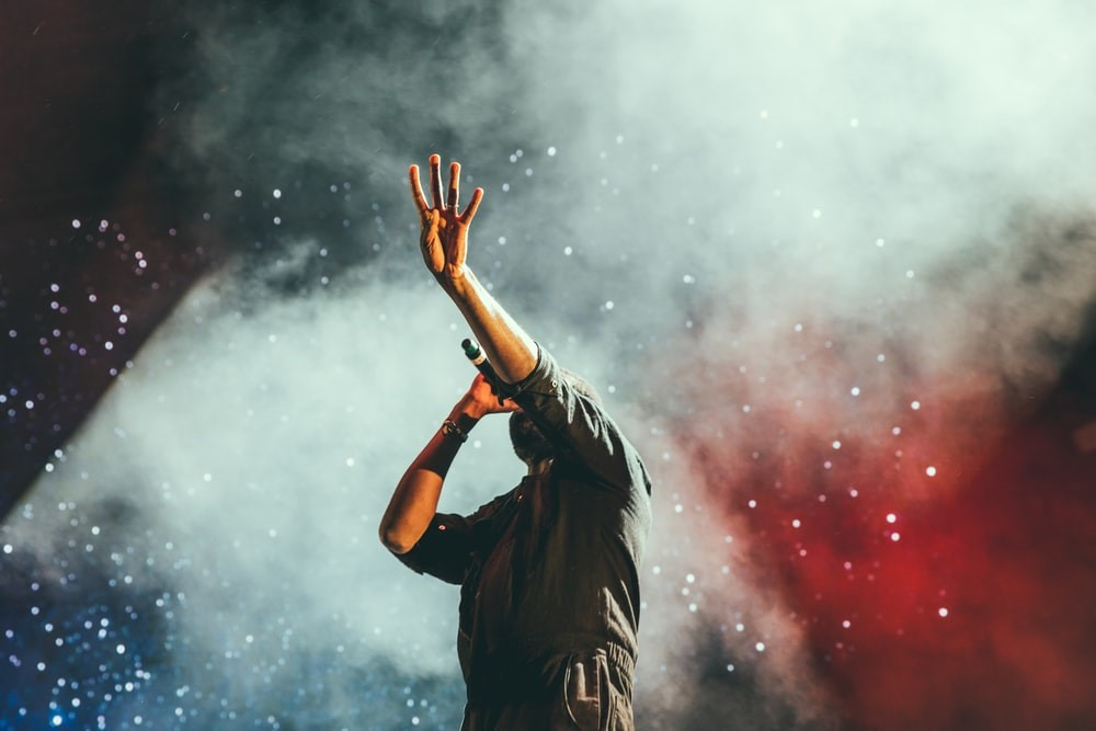 man with microphone, left hand in air obscuring face in front of smokey background