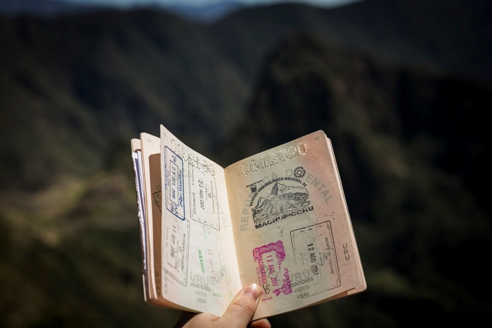 Open passport held with mountains in background