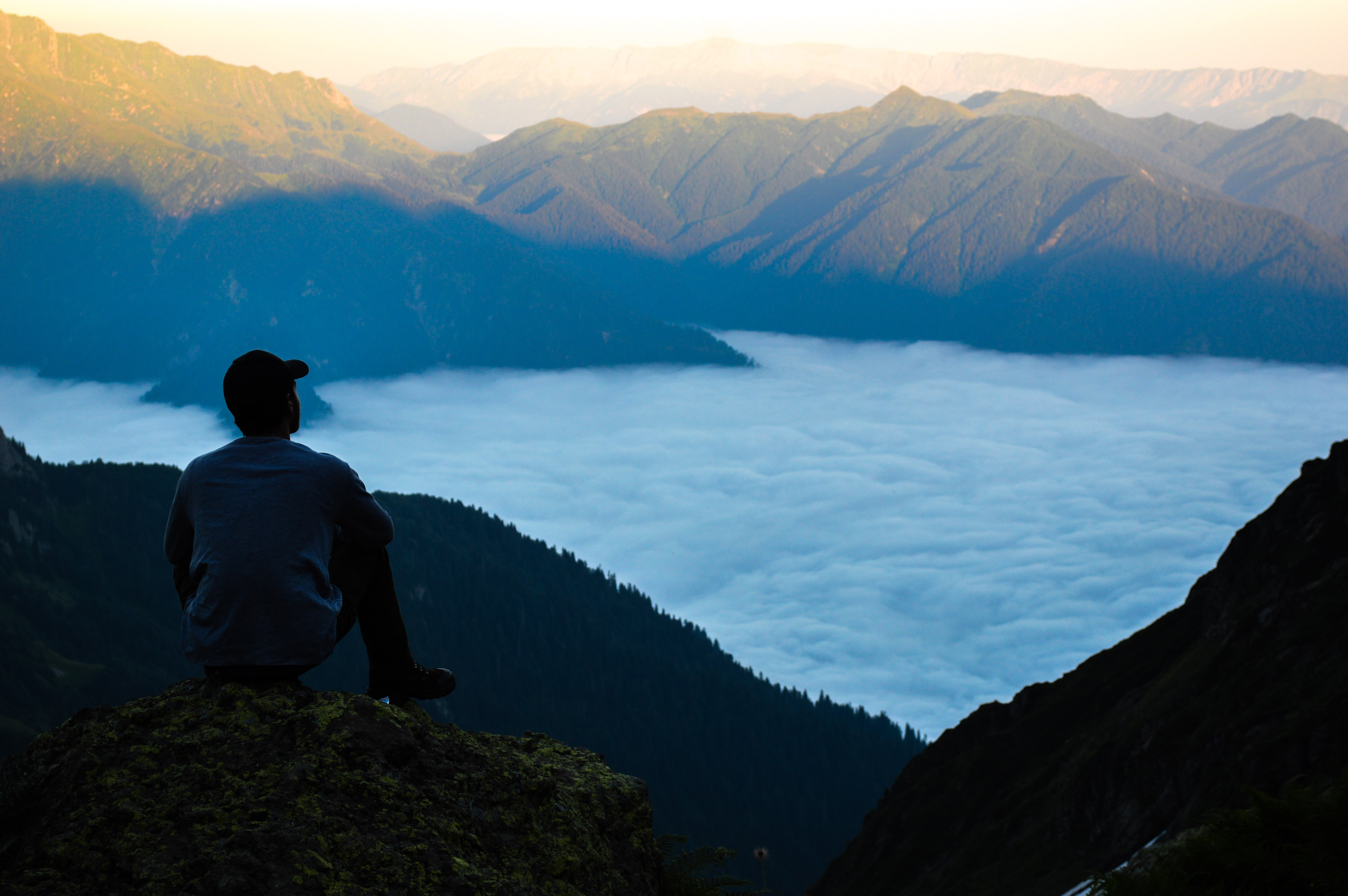 man standing at edge of cliff overlooking lake