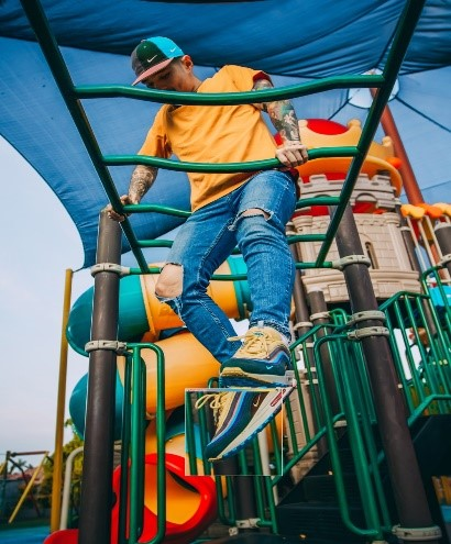 young man in yellow tshirt and jeans on monkey bars in playground