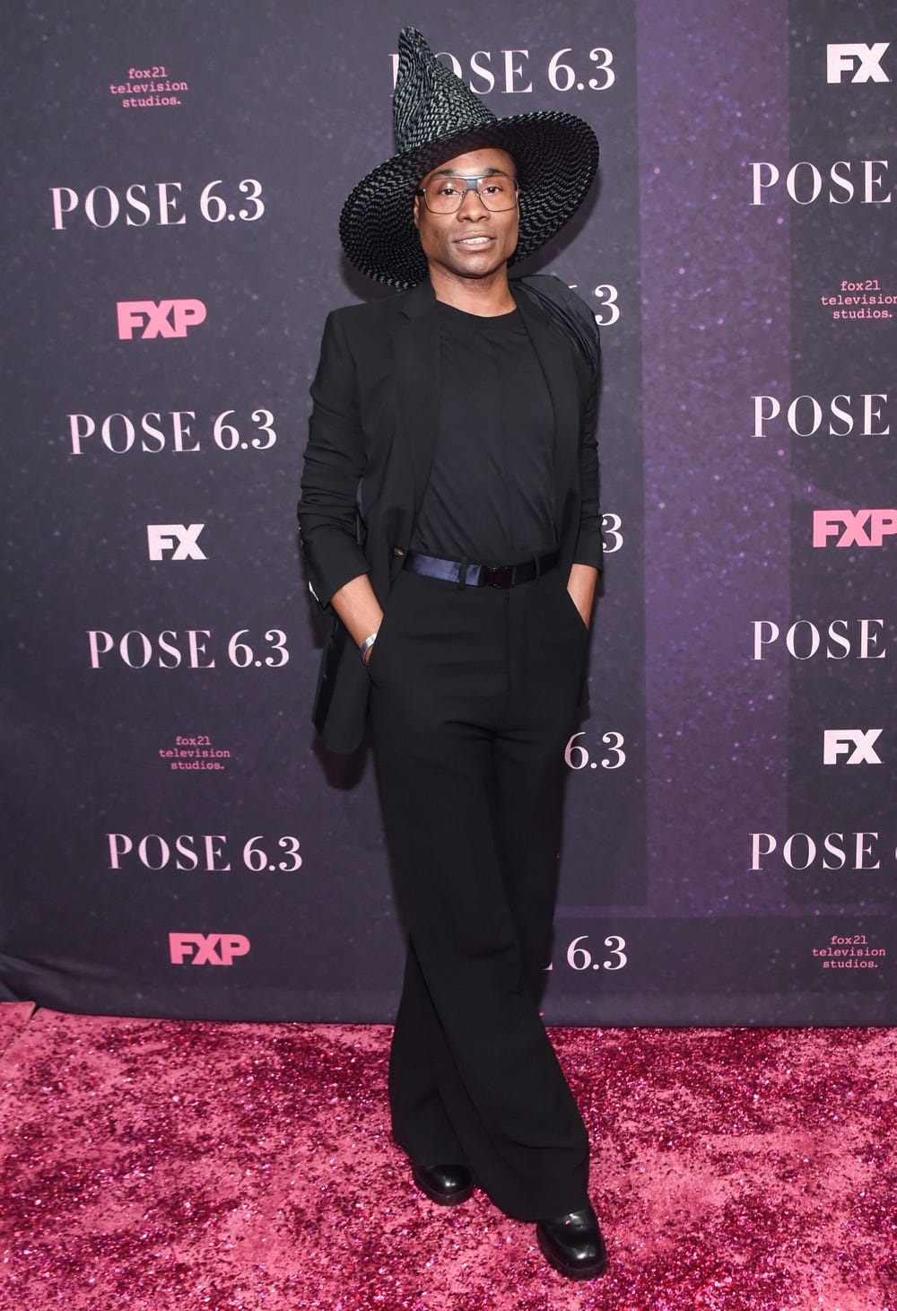 Billy Porter wearing an all black outfit with stylish witch-like hat