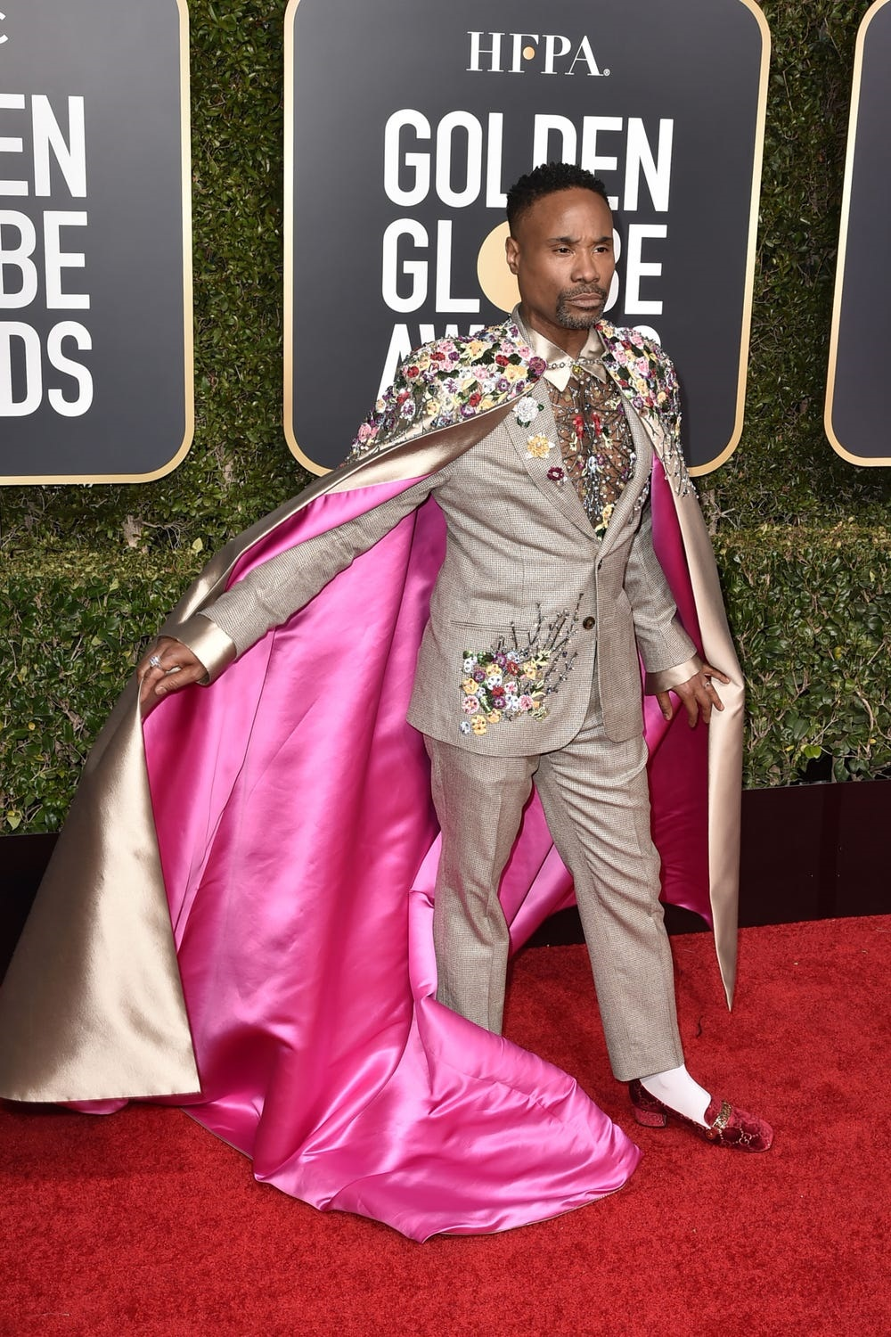 Billy Porter at the 2019 Golden Globes wearing a decorative taupe suit with outstanding pink cape.