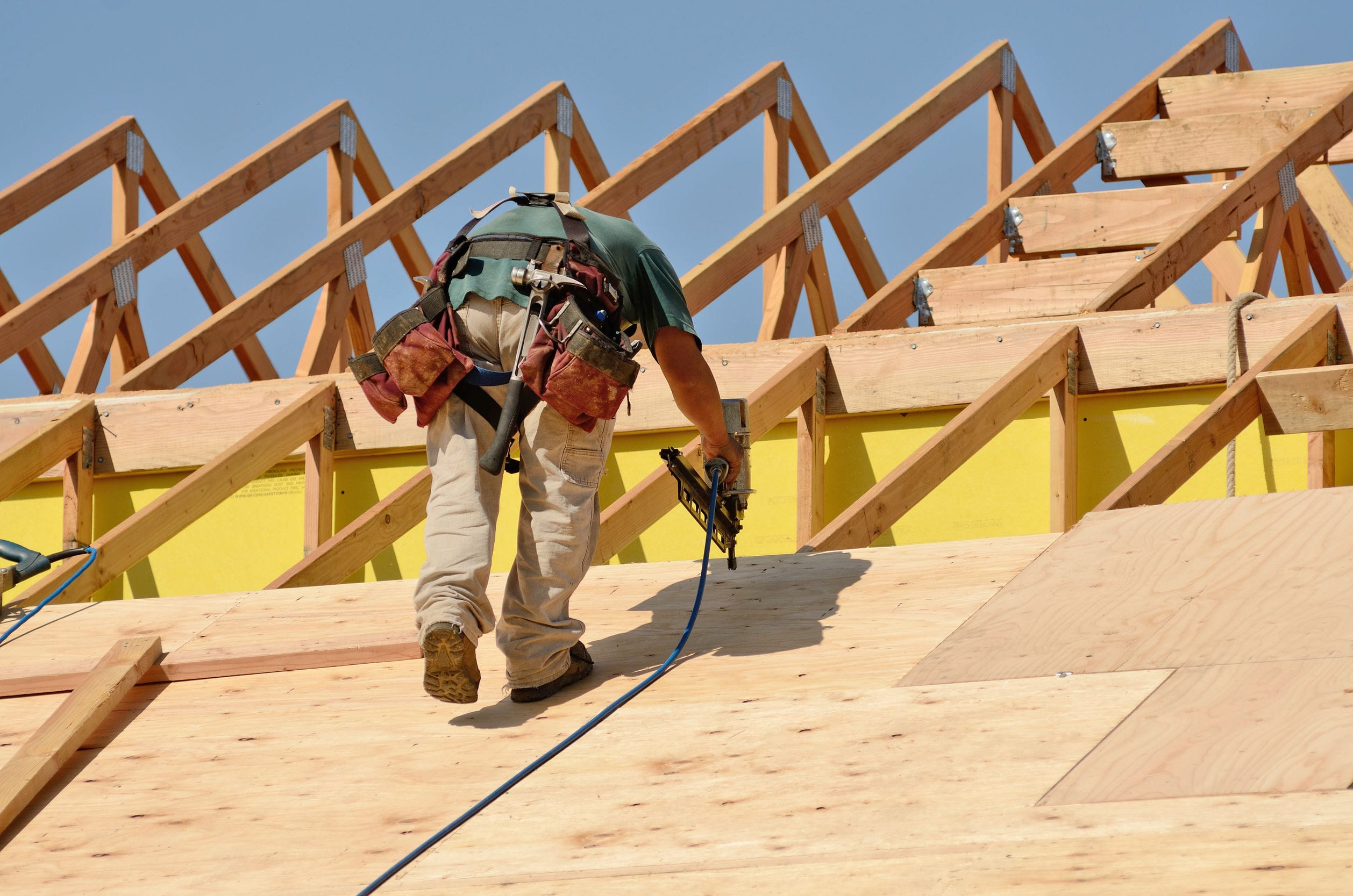 Construction crew working on the roof sheeting of a new, two story, commercial appartment building in Oregon