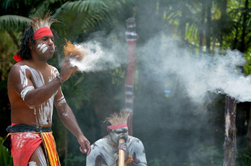 45816576 - yugambeh aboriginal warrior demonstrate  fire making craft during aboriginal culture show in queensland, australia.