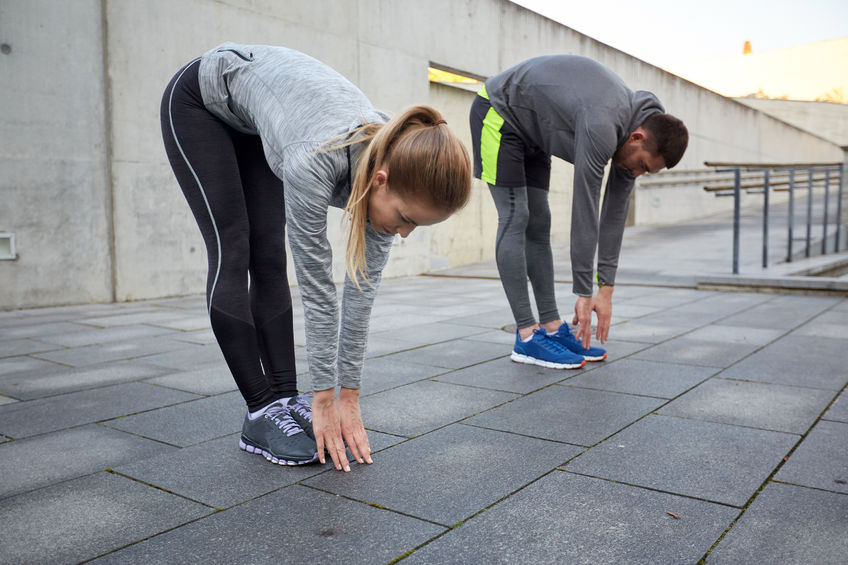 51225200 - fitness, sport, exercising, people and lifestyle concept - couple stretching and bending forward on street