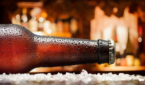"""Ice Cold Bottle  of  Beer , covered with water drops - condensation. Standing on wooden table in the pub."""