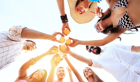 Group of cheerful friends making toast with beer on beach. Young people with casual clothes, girls with bikini and sunglasses. Directly below.