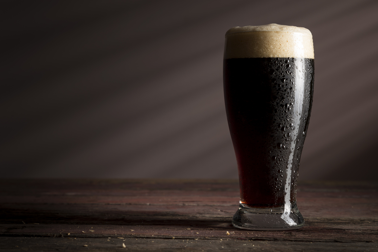 Wet glass of cold dark beer with foam placed on a rustic wooden table.