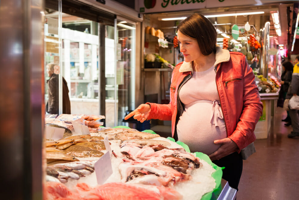 pregnant woman buying fish at the shops