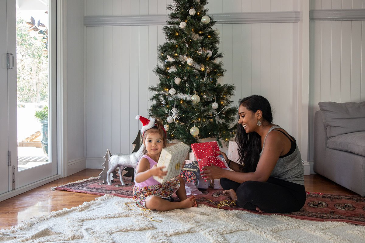 mum and child under christmas tree with presents
