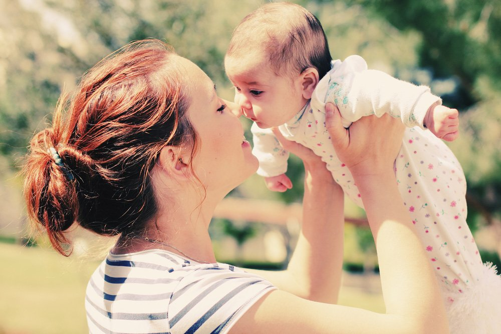 mother-holding-her-baby-outside-l