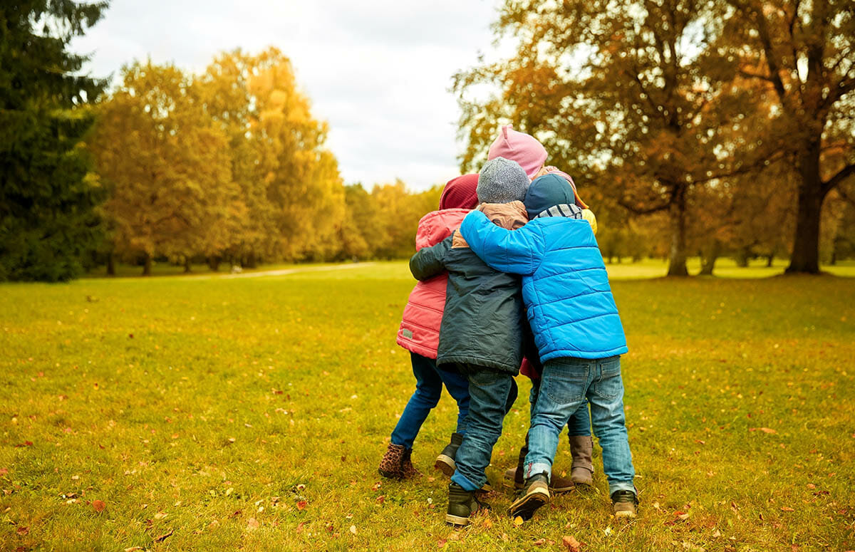 kids-hugging-in-park-cover-the-cost-of-kids
