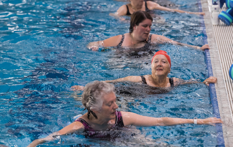 Swimmers doing aquatic aerobics at edge of pool
