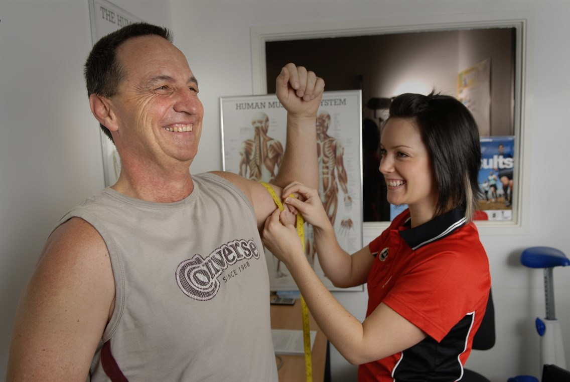 Man getting muscles measured by trainer