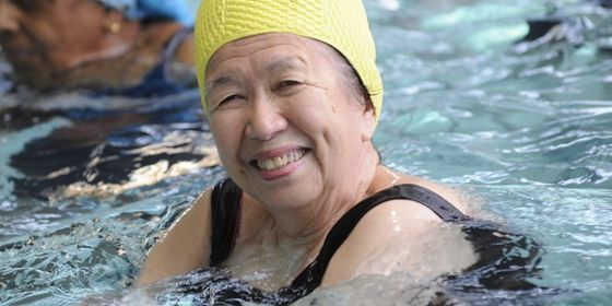 Woman with yellow swimming cap in water