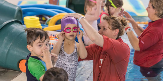 Swimming teacher helping girl put swimming cap and goggles on.