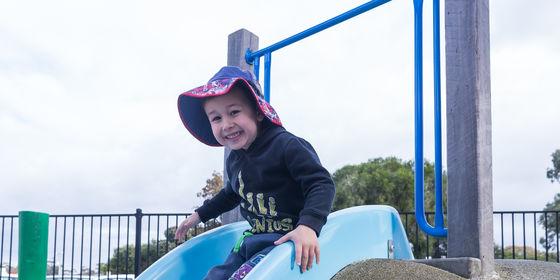 Boy sliding down slide