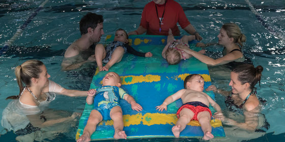 Parents with kids playing on floating foam mats