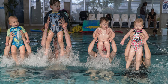 Parents lifting toddlers out of water in air