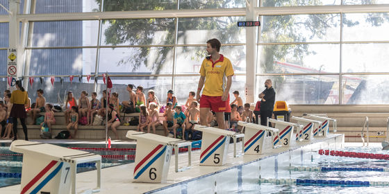 Lifeguard watching over pool with school kids in background