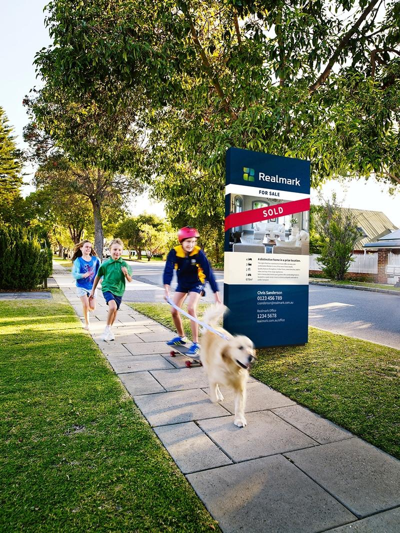 Children running past a property that has been sold by Realmark.