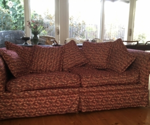 Sofa & seven cushions, upholstered in red fabric