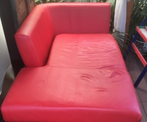 Comfortable but worn red love seat sofa