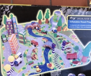 Toy car mat with inflatable buildings, trees, mountain and bridges