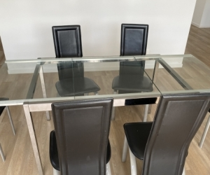extendable glass top dining table and six black chairs